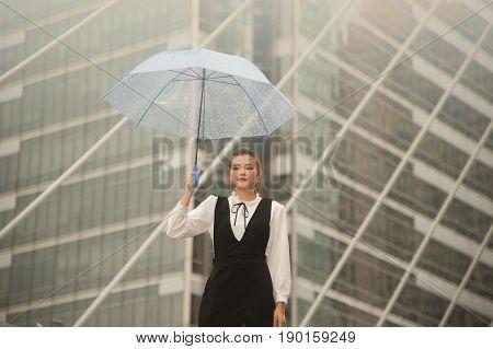 Thai pretty woman in black dress holding transparent umbrella walking on bridge crossing  landmark in Bangkok,Thailand.