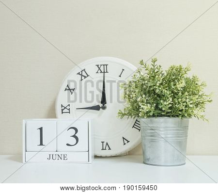White wooden calendar with black 13 june word with clock and plant on white wood desk and cream wallpaper textured background selective focus at the calendar