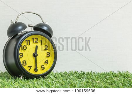 Closeup black and yellow alarm clock for decorate show half past eleven o'clock or 12:30 p.m. on green artificial grass floor and cream wallpaper textured background with copy space