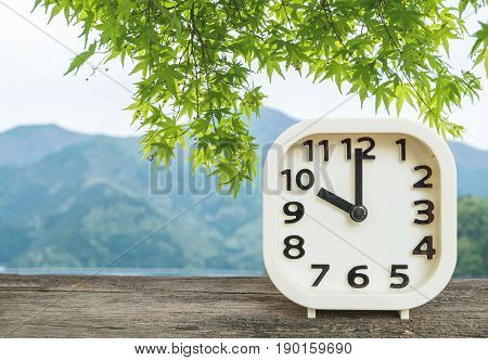 Closeup white clock for decorate in 10 o'clock on blurred mountain view background
