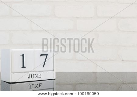 Closeup white wooden calendar with black 17 june word on black glass table and white brick wall textured background with copy space selective focus at the calendar