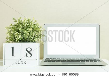 White wooden calendar with black 18 june word with white blank space at center of computer notebook on white wood desk and cream wallpaper textured background selective focus at the calendar