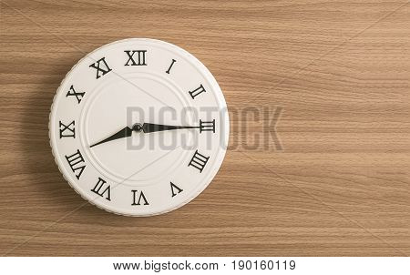 Closeup white clock for decorate show a quarter past eight o'clock or 8:15 a.m. on wood desk textured background with copy space