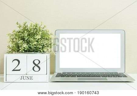 White wooden calendar with black 28 june word with white blank space at center of computer notebook on white wood desk and cream wallpaper textured background in selective focus at the calendar