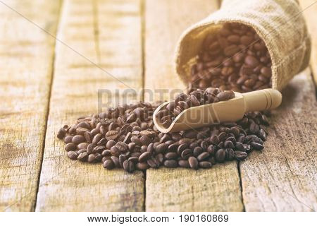 Coffee beans in gunny bag. Close up or macro concept of roasted black coffee beans for background,texture and wallpaper. Pour coffee beans from gunny bag on rustic wood table. Old wood frame with coffee beans in gunny bag for coffee design.