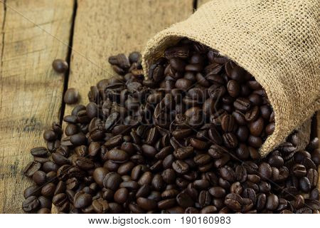 Coffee beans in gunny sack. Close up or macro concept of roasted black coffee beans for background ,texture and wallpaper. Pour coffee beans from gunny sack on rustic wood table. Old wood frame with copy space in coffee beans concept.