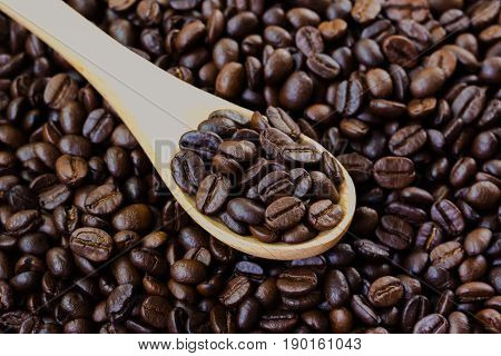 Coffee beans in wood spoon on stack of coffee beans. Close up of coffee beans concept for background and wallpaper. Macro concept of coffee for background and texture. Stack of coffee bean with copy space for about your coffee design.