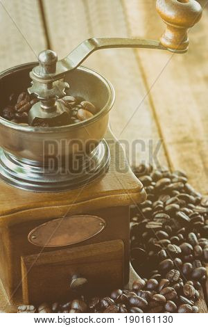 Grinding coffee beans by rotary coffee grinder under morning light with relaxing. Wake up in the morning with homemade fresh coffee. Antique coffee grinders for grinding your coffee bean for breakfast. Made your coffee with coffee grinder.