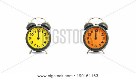 Closeup yellow alarm clock and orange alarm clock for decorate in 12 o'clock isolated on white background