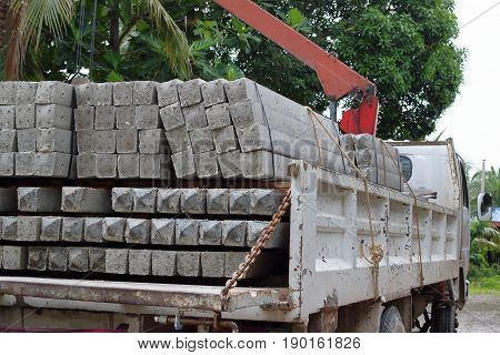 Side view of concrete pole pile load on a truck