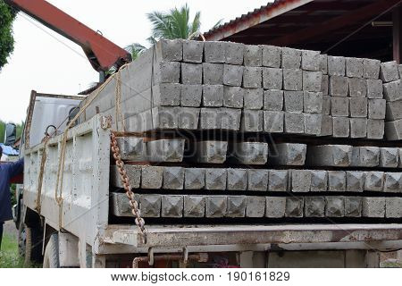 Close up side view of concrete pole pile load on a truck