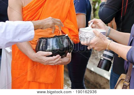 Hands of people while put food to a Buddhist monk's alms bowl in the end of Buddhist Lent Day