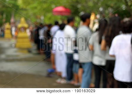 Abstract blurred of people line up at temple in the end of Buddhist Lent Day. Before there put food to a Buddhist monk's alms bowl