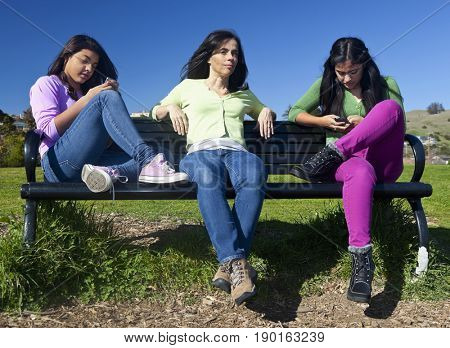 Hispanic mother and daughters sitting on park bench