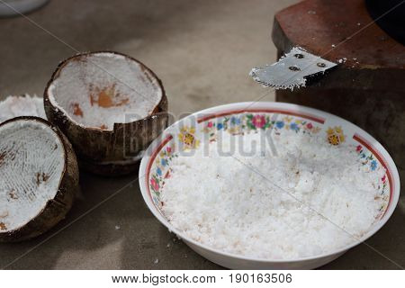 Close up blade of coconut grater with coconut grated in bowl Shallow depth of field light and shadow
