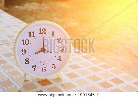 White clock at 8am on the tiled floor and seashore background Freedom concept Sunshine effect Vintage tone