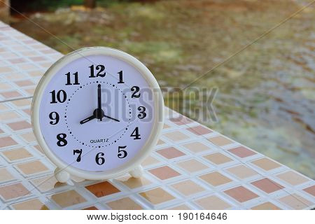 White clock at 8am on the tiled floor and seashore background Freedom concept