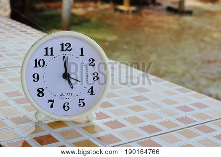White clock at 5pm on the tiled floor and seashore background Freedom concept