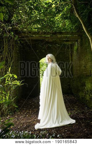 Caucasian woman wearing white cloak in garden