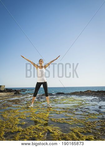 Mixed race runner stretching on rocky beach