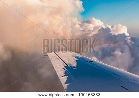 Aerial view of golden big and fluffy cumulonimbus cloud lit by the evening sun over Florida view from the aircraft during the flight.