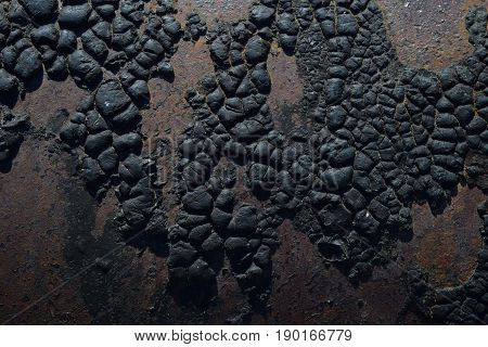 Rusty steel metal wall with heavy corrosion background and black tar pattern