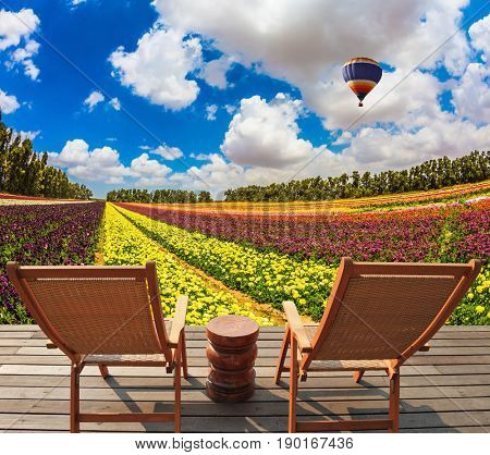 Wooden chaise lounges  in the meadow with flowers. Huge balloon flies over the field. Concept of ecological tourism. Rural rest