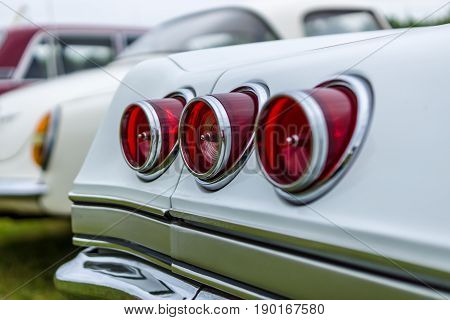Rear stoplights of a vintage car. Focus on the center.