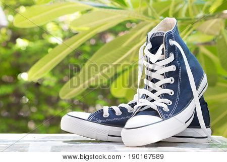 Pair of new blue sneakers on table top perspective and naturel background