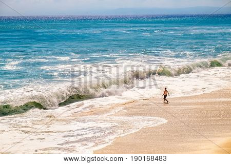Young fit man going to swim in colorful sea with sunny blue sky on horizon at Bali island, Indonesia. Outdoor nature landscape of huge ocean waves and clear white sand beach in Southeast Asia.