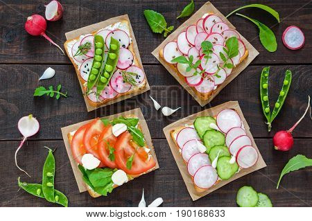 Several kinds of sandwiches with vegetables: radish tomatoes cucumber arugula on crispy toast on a dark wooden background. Top view. Vegetarian dish. Proper nutrition. Healthy food. Breakfast.