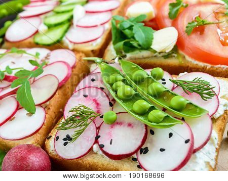 Several kinds of sandwiches with vegetables: radish tomatoes cucumber arugula on crispy toast on a dark wooden background. Vegetarian dish. Proper nutrition. Healthy food. Breakfast.