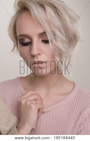 Close-up Portrait In A Half Turn Girls Blonde With Dark Eye Makeup And Short Hair In A Light Pink Sw