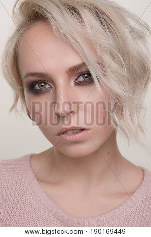 Close-up Portrait Of Blonde Girl With Dark Eye Makeup And Short Hair In A Light Pink Sweater Looking