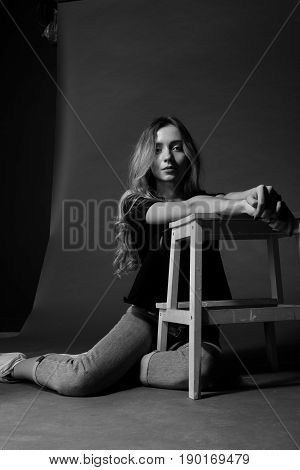 Black And White Portrait Of Blonde Girl In T-shirt And Jeans Sitting On The Floor Leaning On Chair A