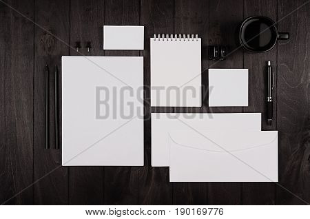 Dark elegance working space with blank notepad letterhead business card coffee cup and earphone on black wood plank background. Template for your design.