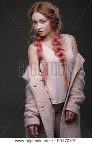 The Girl With Pink Hair In Braids, And Pink-blue Makeup With A Pink Coat Worn Off The Shoulder Is On