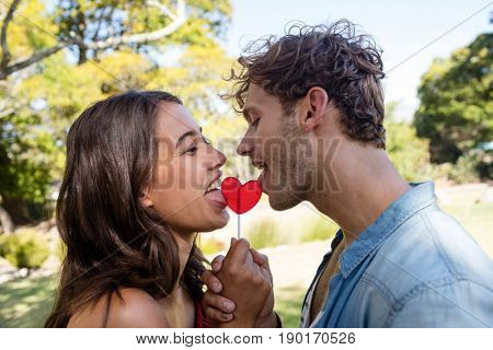Romantic couple licking a heart shaped lollypop in park on a sunny day