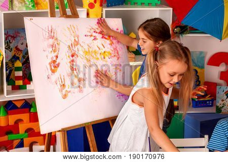 Children painting finger on easel. Group of kids girl learn paint in class school. Kindergarten interior on background. Picture with prints of children's hands.