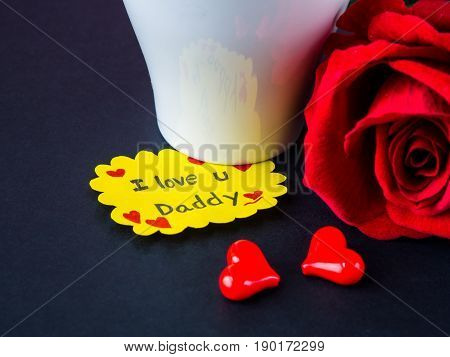 Father's day concept. I LOVE YOU DADY message with red rose two red heart and gift on black background