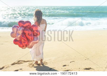 Young woman in white dress holding red balloons on the beach, enjoying sunny windy day. Rear view.