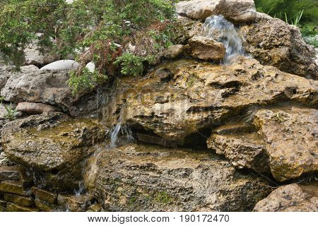 Composition of small artificial waterfall and stones in park.