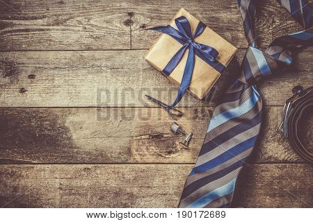 Father's day concept - present, tie on rustic wood background, top view