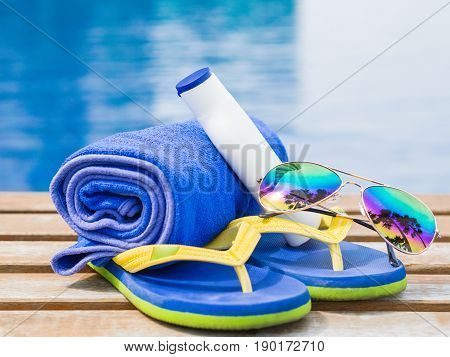 flip flops sunglasses blue towel and sunscreen at the side of swimming pool. Vacation beach summer travel concept