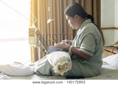 A Asia Woman In Hospital Room In Bed Sick And Injured Using Internet In Computer Laptop Feeling Conc