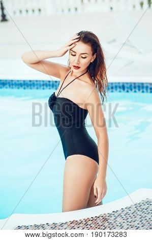 Elegant sexy woman in the white bikini on the slim and shapely body is posing near the swimming pool in private villa. Sexuality beauty. Hot weather outside time to have rest and swim in pool.