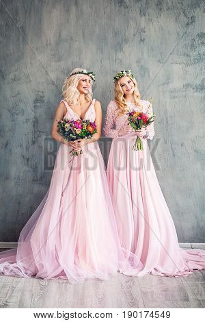 Blonde Beauty. Perfect Fashion Model Women in Pink Dress on Grey Background. Perfect Girls and Summer Flowers