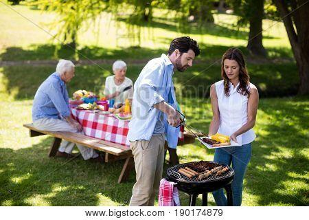 Couple preparing barbeque in park