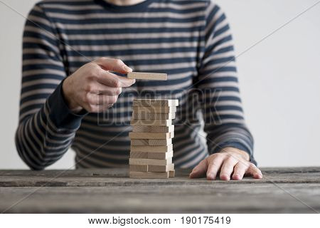 Man in stripped sweater placing wooden domino in a tower. Conceptual of vision and planning.