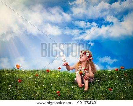 Little girl sitting on green grass and squinting in the sun. The child keeps on hand a butterfly and a bouquet of flowers. In a field of red poppies and daisies. Blue sky